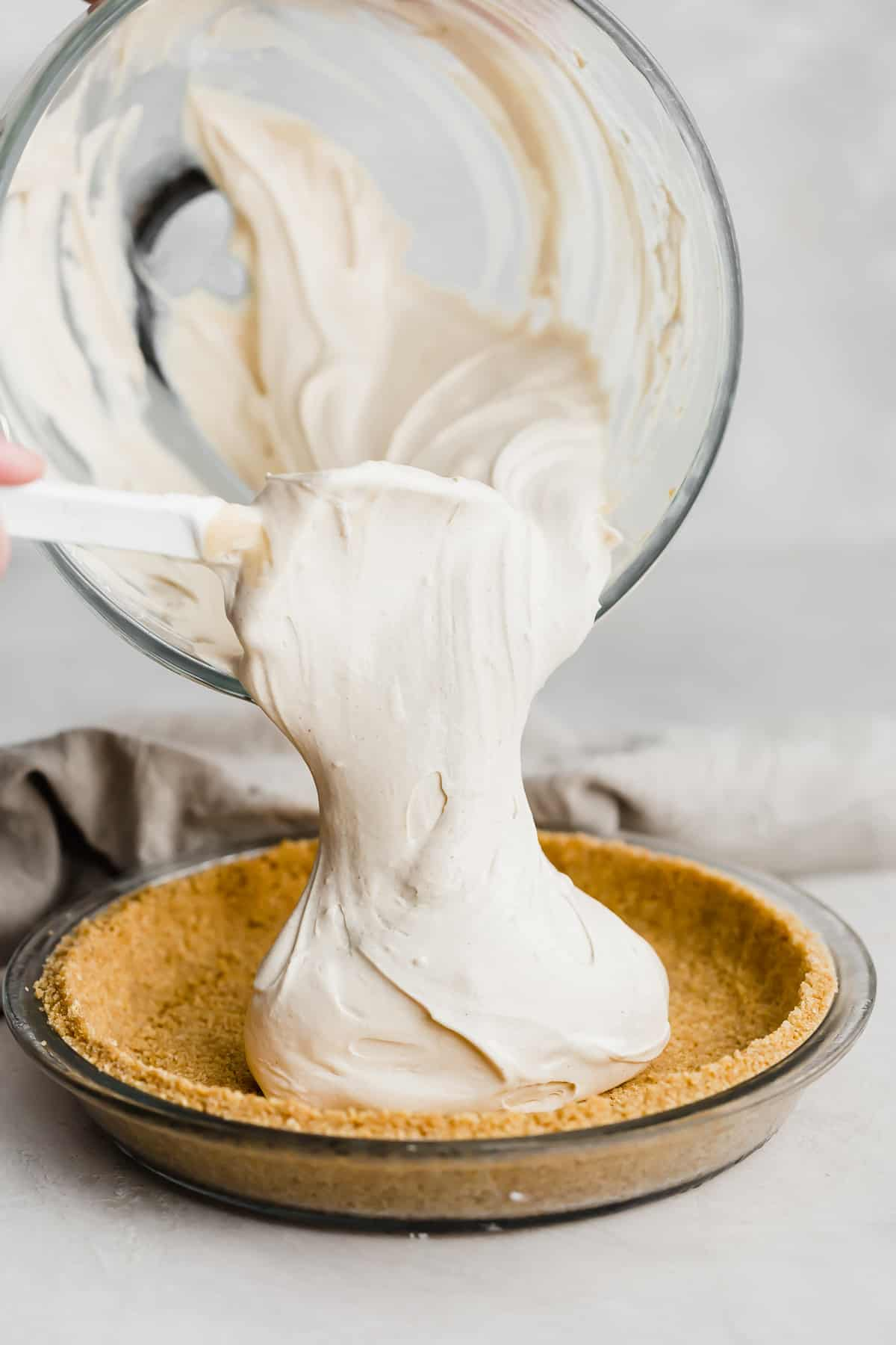 A light tan colored peanut butter mixture being poured into a graham cracker crust.