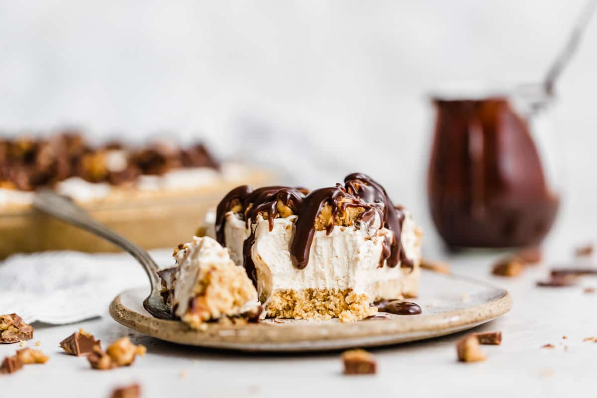A No-Bake Peanut Butter Pie on a plate with a fork having cut into the tip of the pie slice.