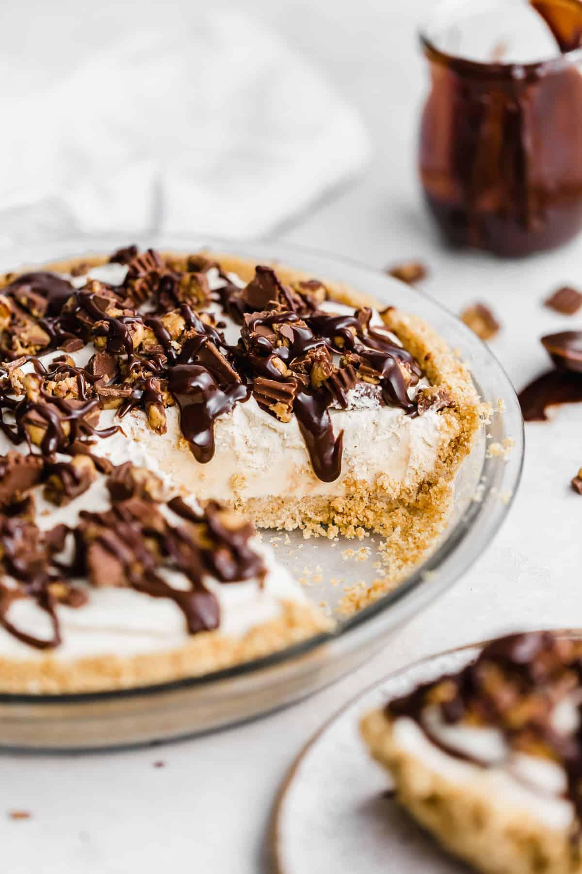 Hot fudge drizzled overtop a No-Bake Peanut Butter Pie in a graham cracker crust.