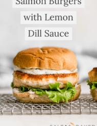 A salmon burger on a bun with lemon dill sauce and lettuce.