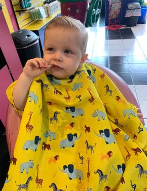 Little boy eating a sucker while getting hair cut.