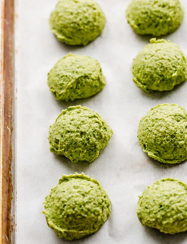 Scoops of green falafels on a baking sheet, prior to baking.
