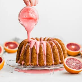 A blood orange glaze being drizzled overtop a blood orange cardamom Bundt Cake.