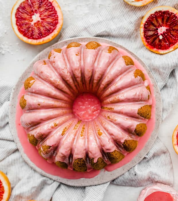 An overhead photo of a blood orange cardamom Bundt Cake topped with a pink blood orange glaze.
