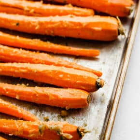 A close up photo of peeled long stem carrots on a baking sheet.