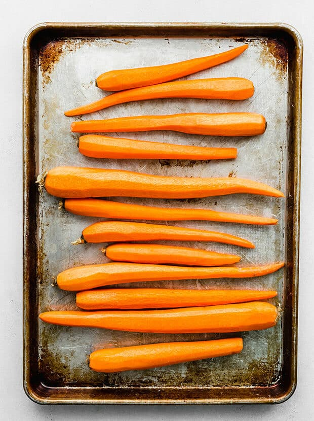Long peeled carrots on a baking sheet.