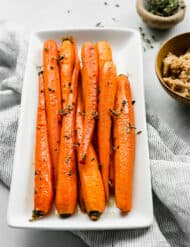 Brown Sugar Roasted Carrots with a garnish of fresh thyme on a white plate.