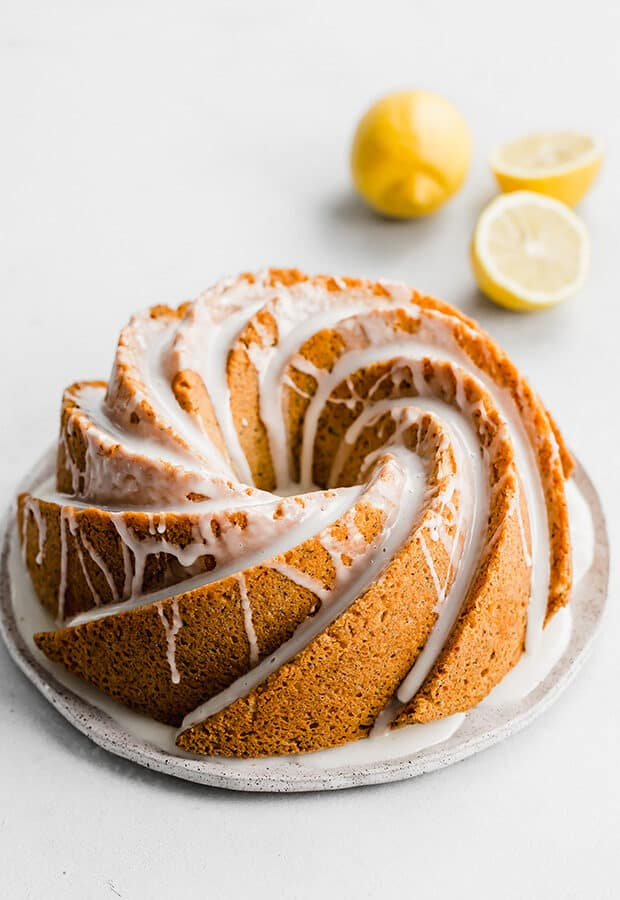 A ,Lemon Poppy Seed Bundt Cake covered in a lemon glaze against a white background.