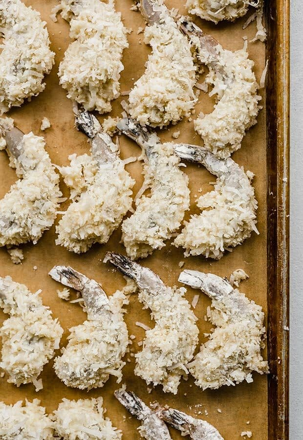 Raw shrimp dipped in a batter and coconut bread crumb mixture, sitting on a baking sheet.