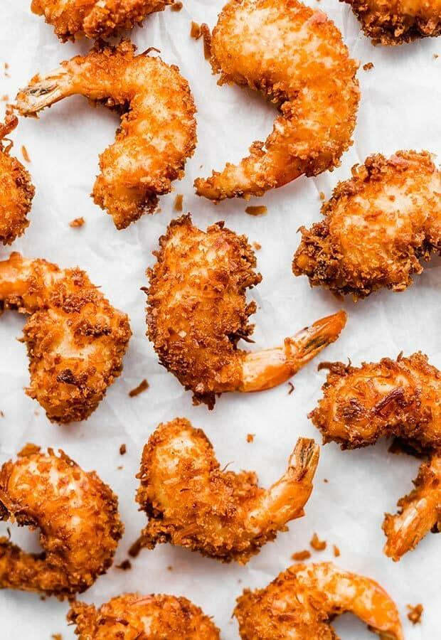 Golden coconut shrimp against a white background.