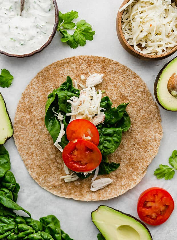A wheat tortilla topped with spinach, chicken, and sliced tomatoes.