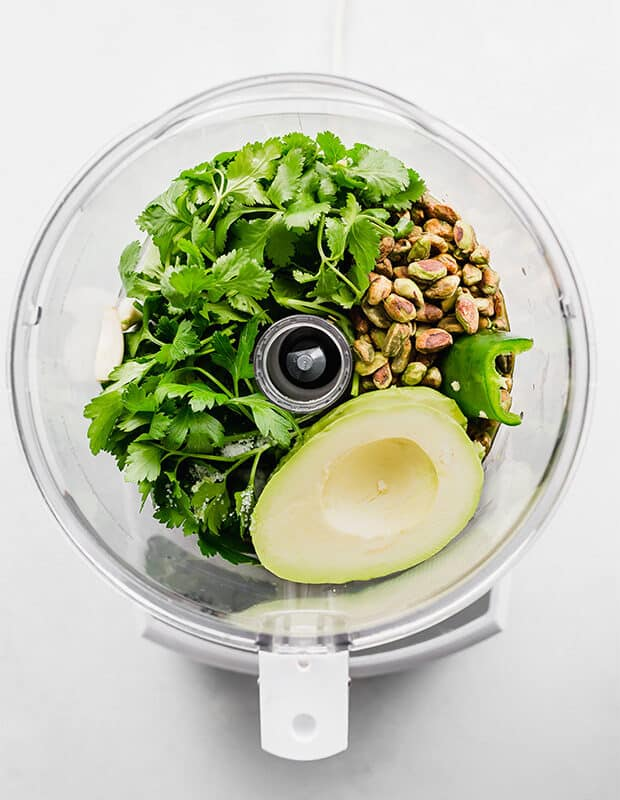 Ingredients to make green sauce in the bowl of a food processor.