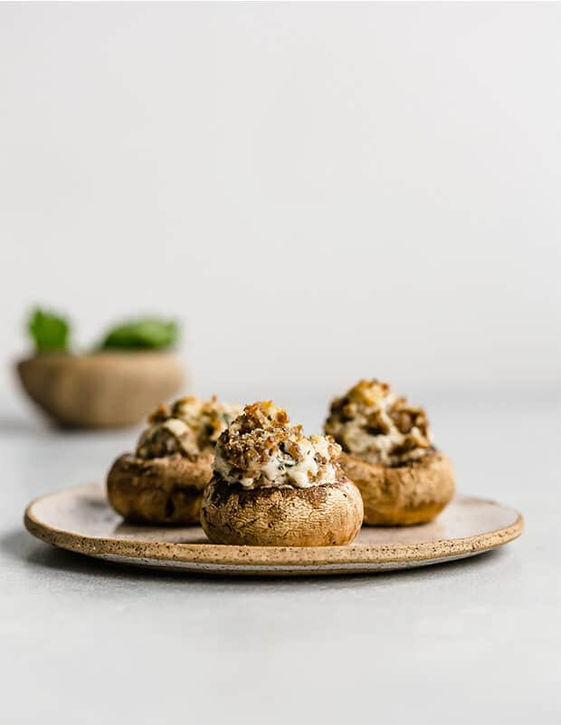 3 stuffed mushrooms on a plate against a white background.