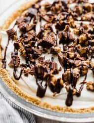 A No-Bake Peanut Butter Pie topped with hot fudge and chopped peanut butter cups.