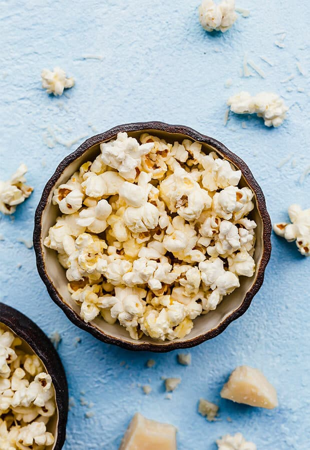 Parmesan popcorn in a bowl, against a blue background.