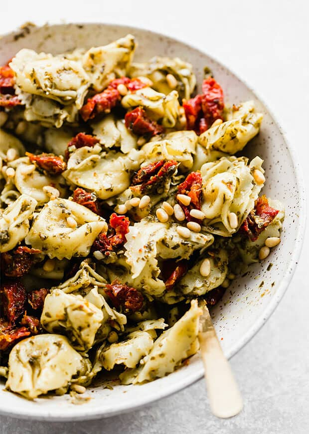A close up photo of Pesto Tortellini Pasta Salad with sun dried tomatoes and roasted pine nuts.
