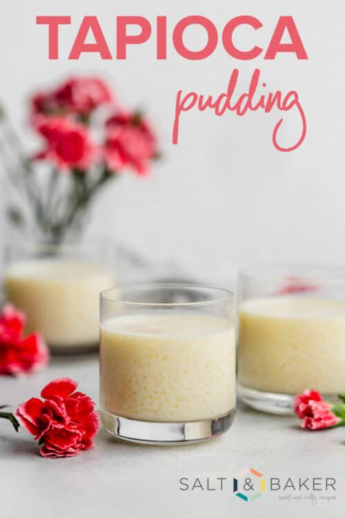 A small glass cup full of tapioca pudding, surrounded by pink flowers.