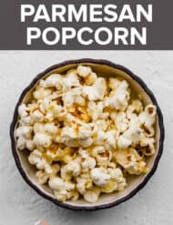 A bowl of parmesan popcorn against a white background.