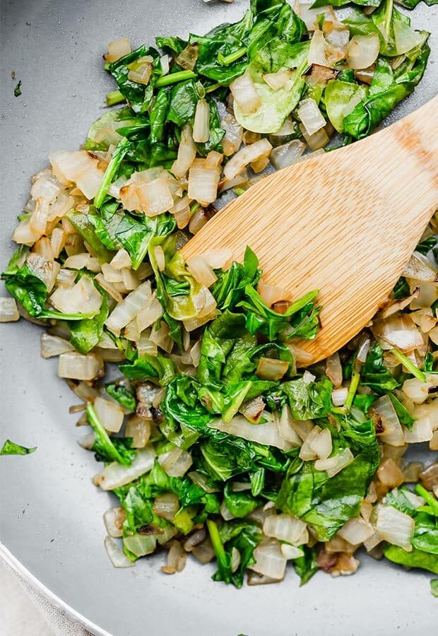 Sauted onions and spinach in a skillet.