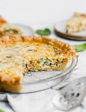 A pie pan with a Spinach and Bacon Quiche.