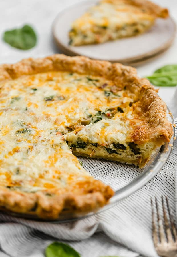 A slice of spinach and bacon quiche in a pie plate.