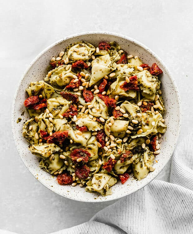 A bowl of Pesto Tortellini Pasta Salad against a white background.