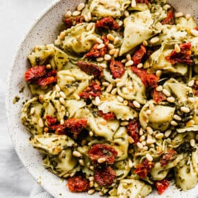 Pesto tortellini topped with sun dried tomatoes and pine nuts.