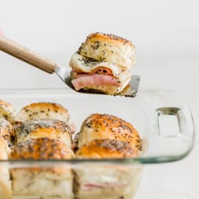 A spatula holding up a baked ham and cheese slider.