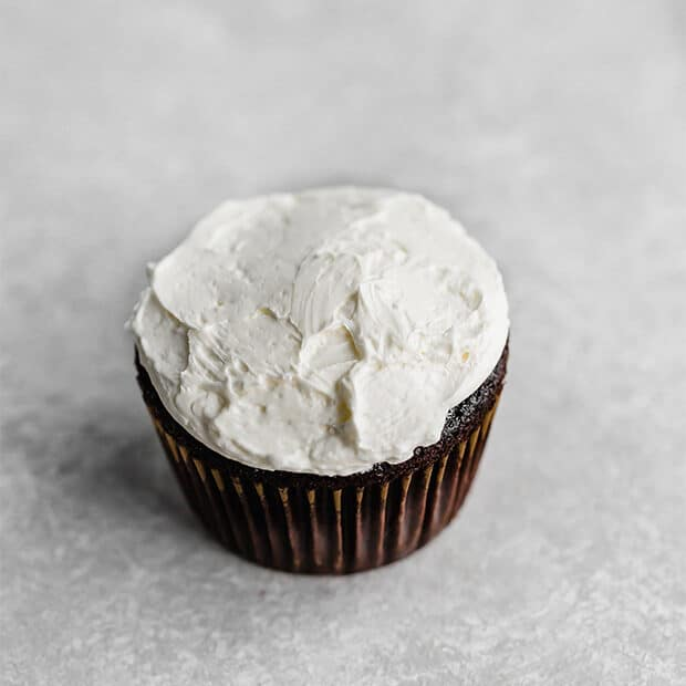 A chocolate cupcake covered in white Swiss meringue buttercream frosting.