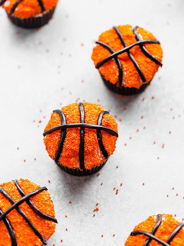 Chocolate cupcakes covered in Swiss meringue buttercream, orange sprinkles and black licorice laces to replicate a basketball.
