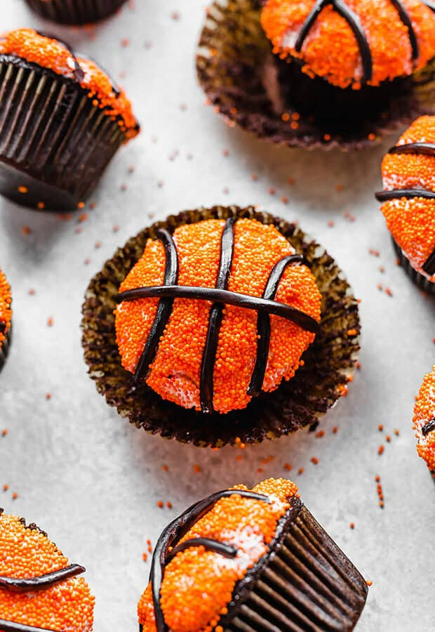 A chocolate cupcake decorated to look like a basketball.