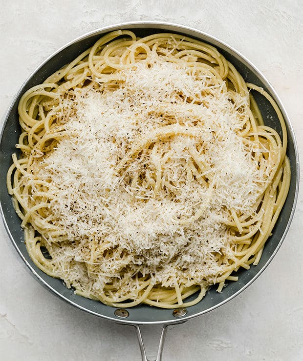 A skillet with bucatini pasta and grated parmesan cheese.