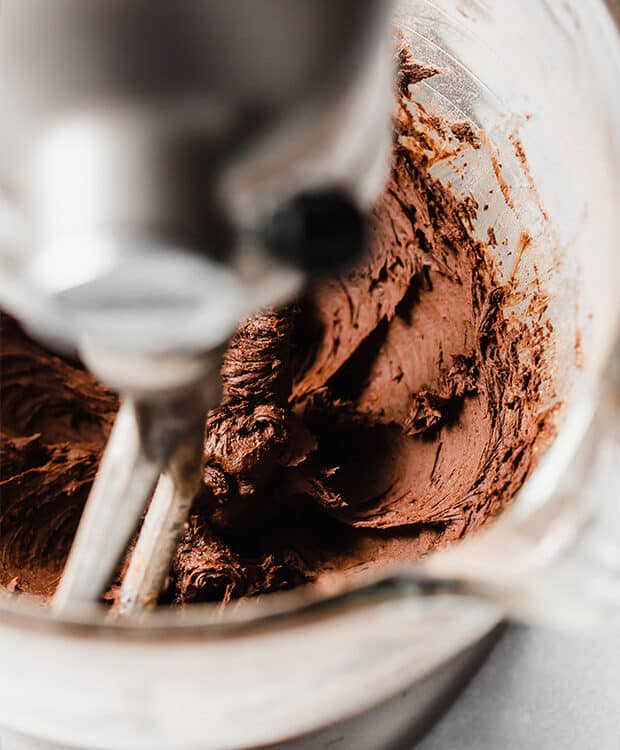 A kitchen aid mixing chocolate frosting.