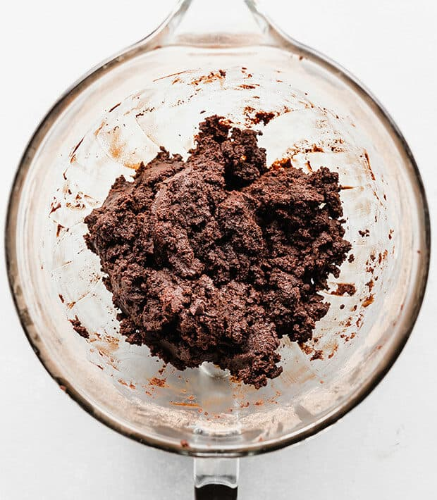 A glass bowl full of chocolate cake mixed with chocolate frosting, for making cake pops.