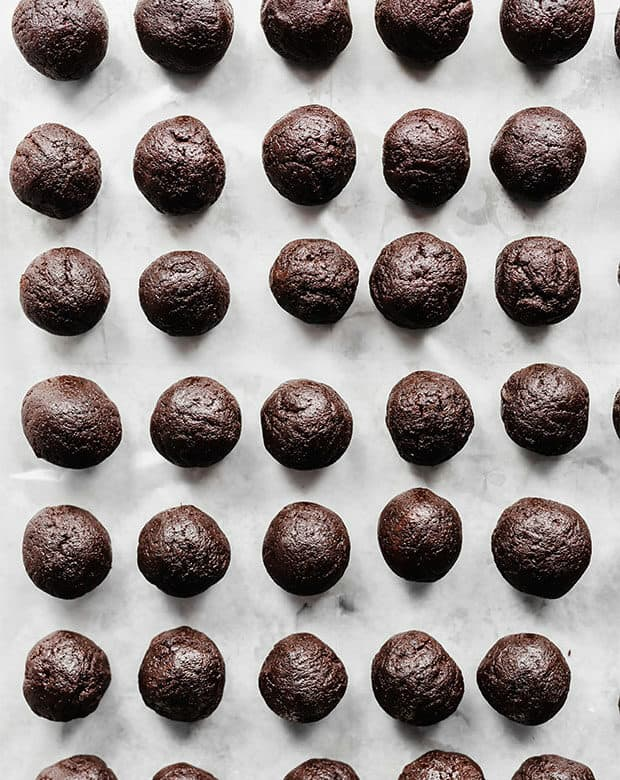 A baking sheet lined with round Chocolate Cake Pops.
