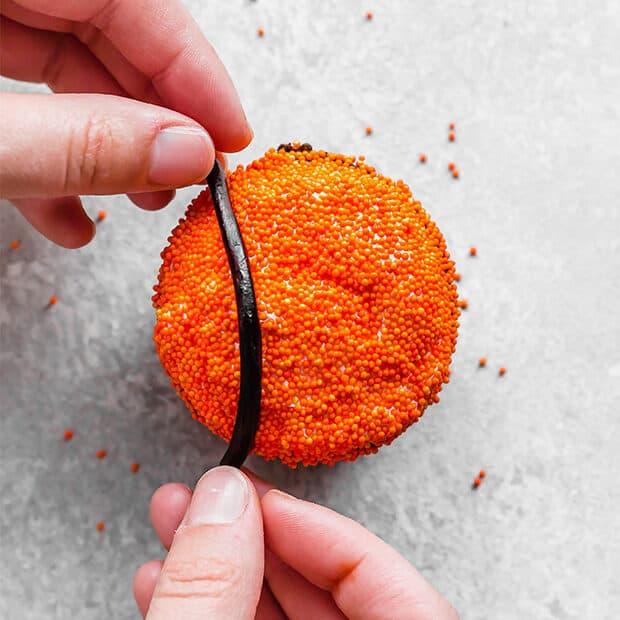 A cupcake covered in orange sprinkles.