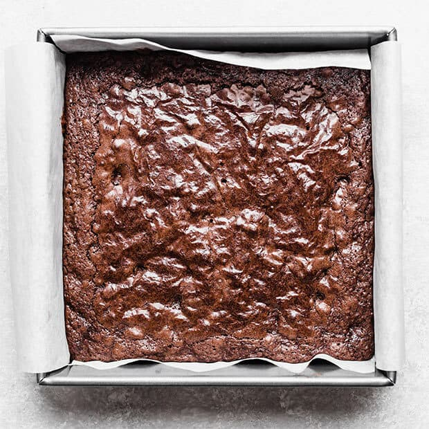Freshly baked brownies in a square brownie pan.
