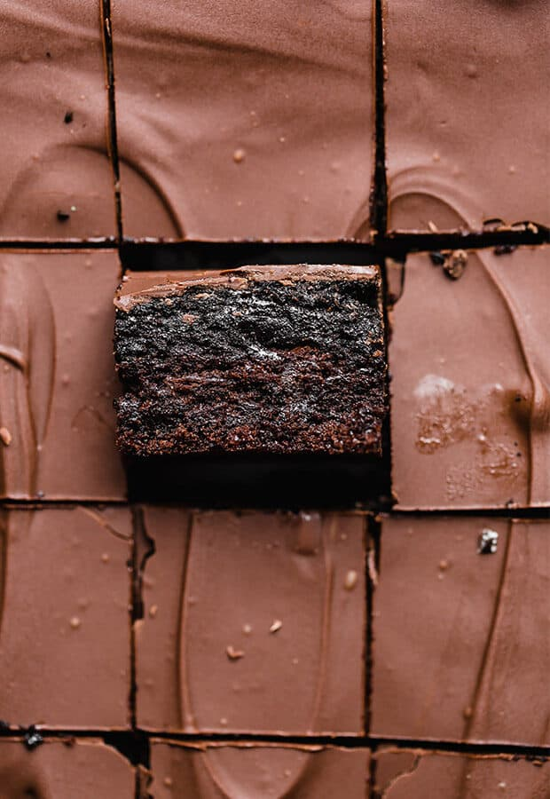 An Oreo truffle brownie on its side, showing the layer of brownie, Oreo truffle, and melted chocolate coating.