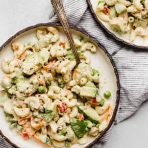 A macaroni salad loaded with vegetables on a plate.
