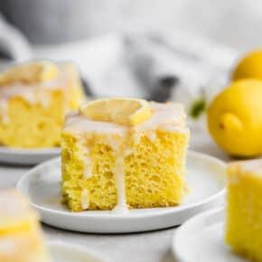 A slice of lemon jello cake topped with a lemon glaze.