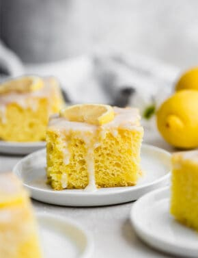 A slice of lemon jello cake topped with a lemon glaze.