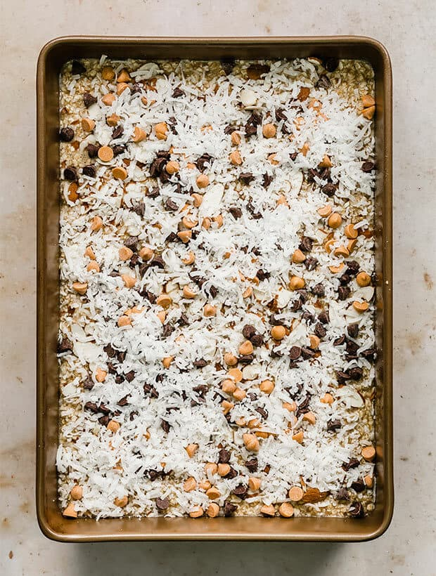Oatmeal cake topped with coconut, almonds, chocolate and butterscotch chips.