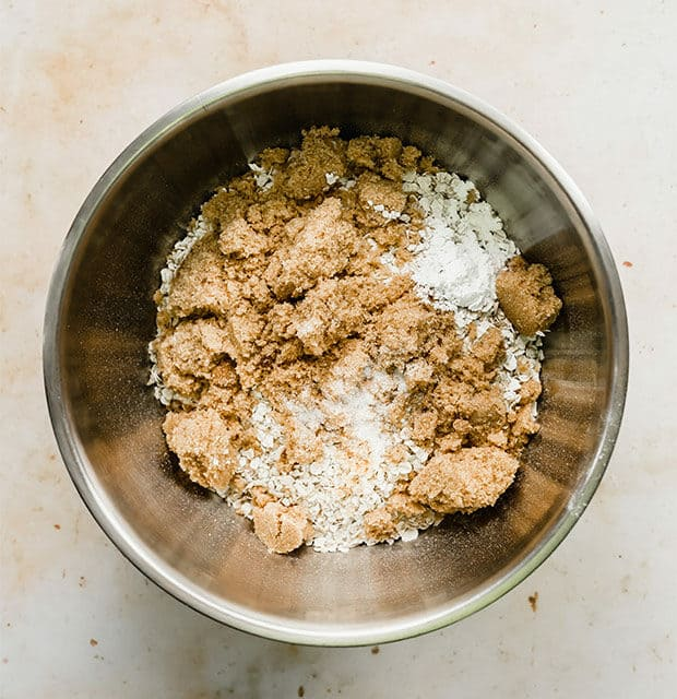 A bowl full of oats, brown sugar, and other dry ingredients.