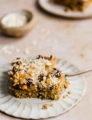 A slice of baked oatmeal cake topped with chocolate chips, coconut, and hemp hearts.