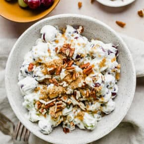 Overhead photo of creamy grape salad topped with brown sugar and chopped pecans.