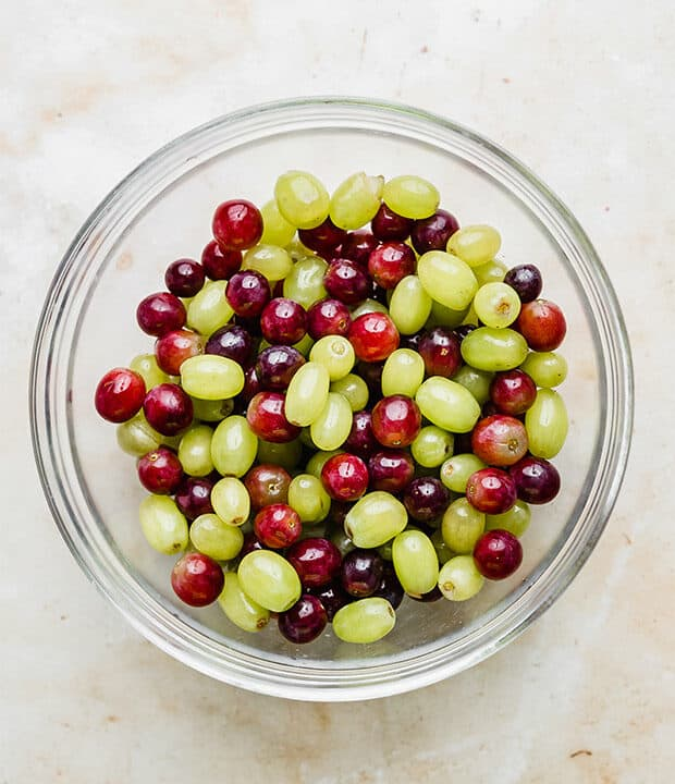 Green and red grapes in a glass bowl.