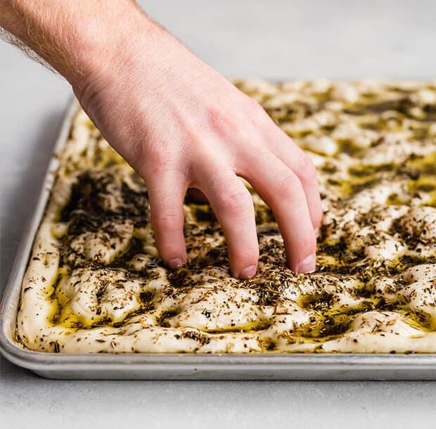 A hand dimpling the focaccia bread dough.