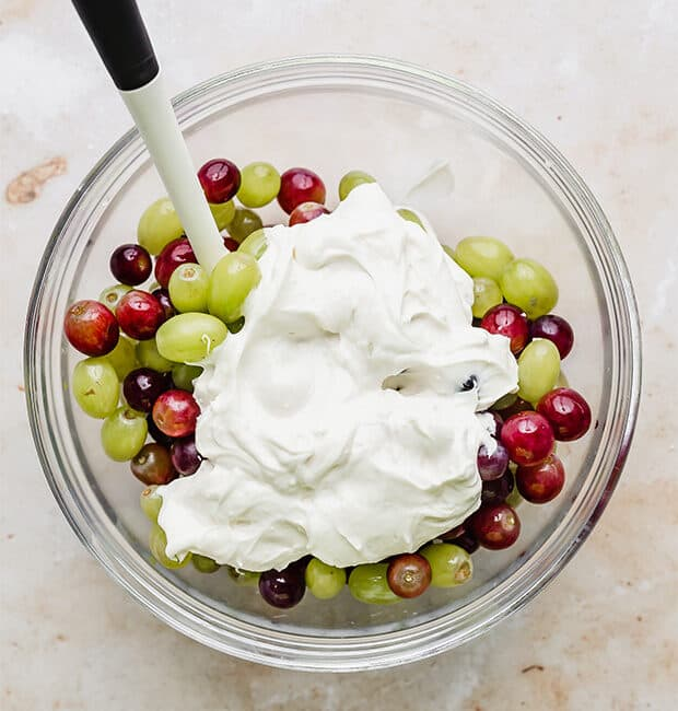 A sweet white sauce plopped on top of a bowl of red and green grapes.