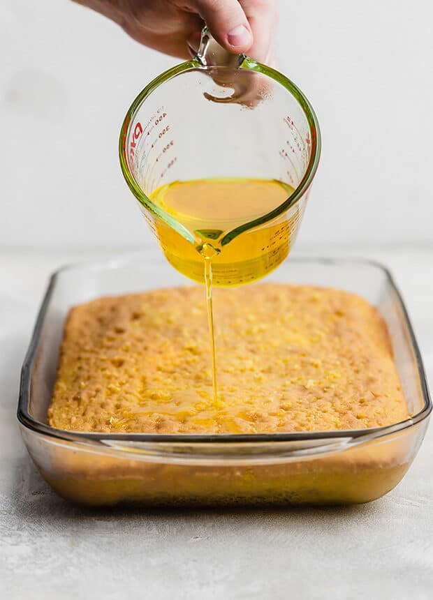 Lemon Jello liquid being poured overtop a baked lemon cake.