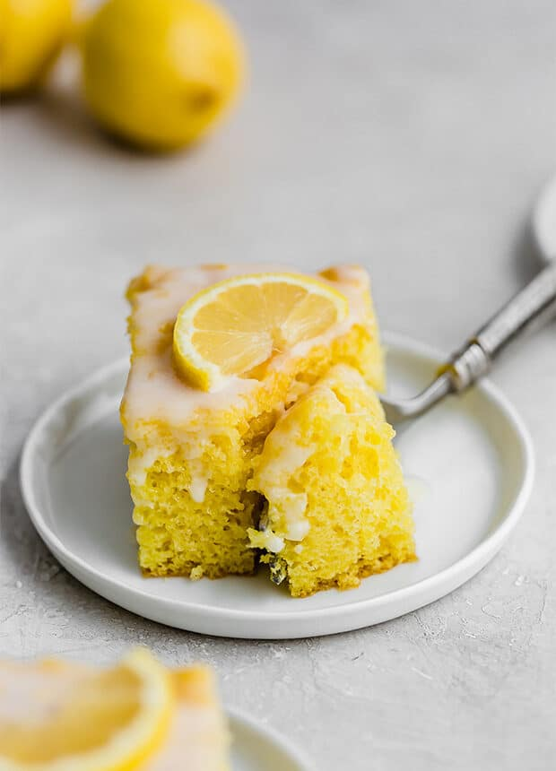A fork cutting into a slice of glazed Lemon Jello Cake.